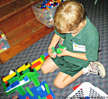 First day, boy playing with stickle bricks